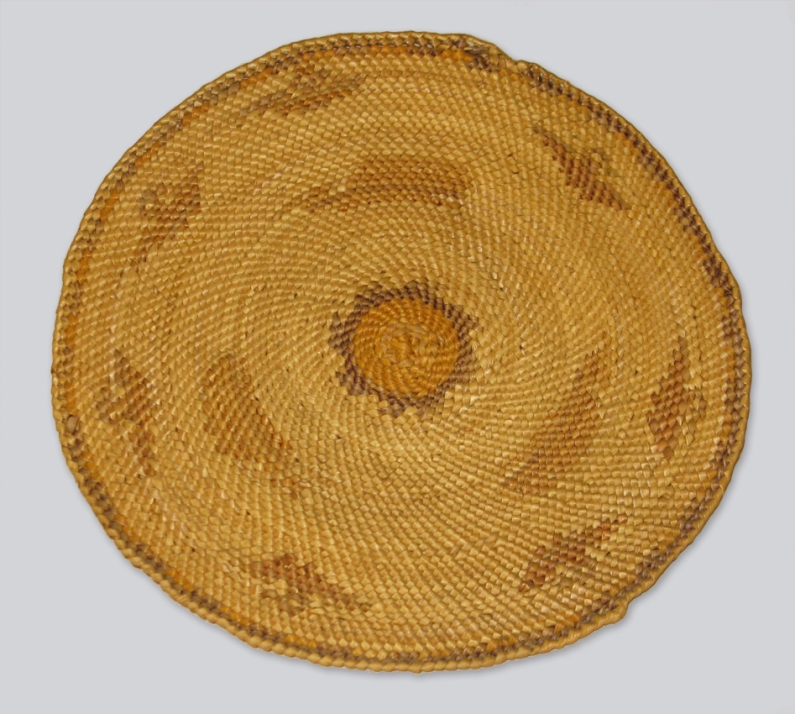 A round mat of woven golden brown grass using a distinctive weaving method that mimics the sun with lines radiating from the centre.