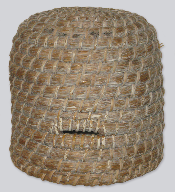A cylindrical bee hive, tightly woven from reeds and featuring a small opening near the bottom for bees to enter and exit.