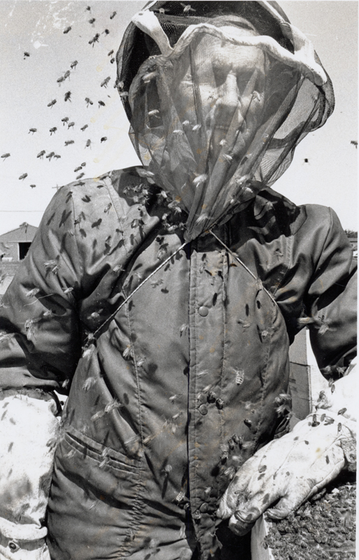 Black and white photo of man smiling while in protective bee gear, with a large swarm of bees surrounding him.