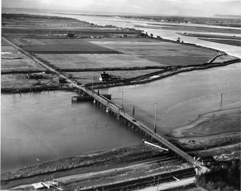 Aerial photo of Canoe Pass, with a bridge over the Fraser river and a landscape of farms in the background.