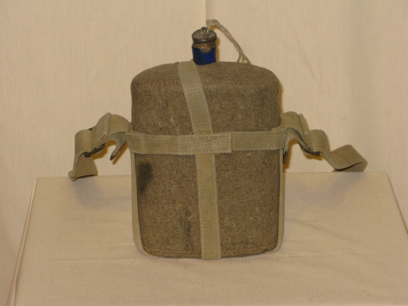 A more modern style of canteen-style water jug, covered in fabric for protection and with a nylon carrying strap.