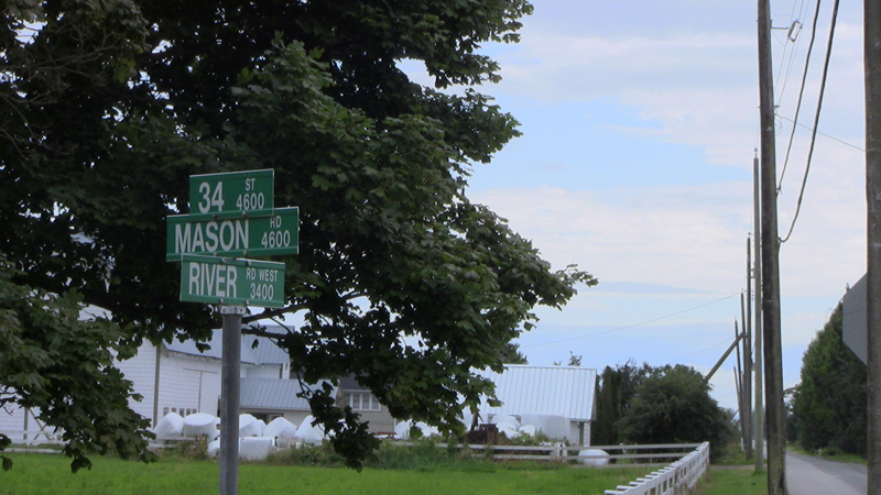 Street signs in a typically rural setting. One sign reads Mason Road, named after the family that produced this quilt.