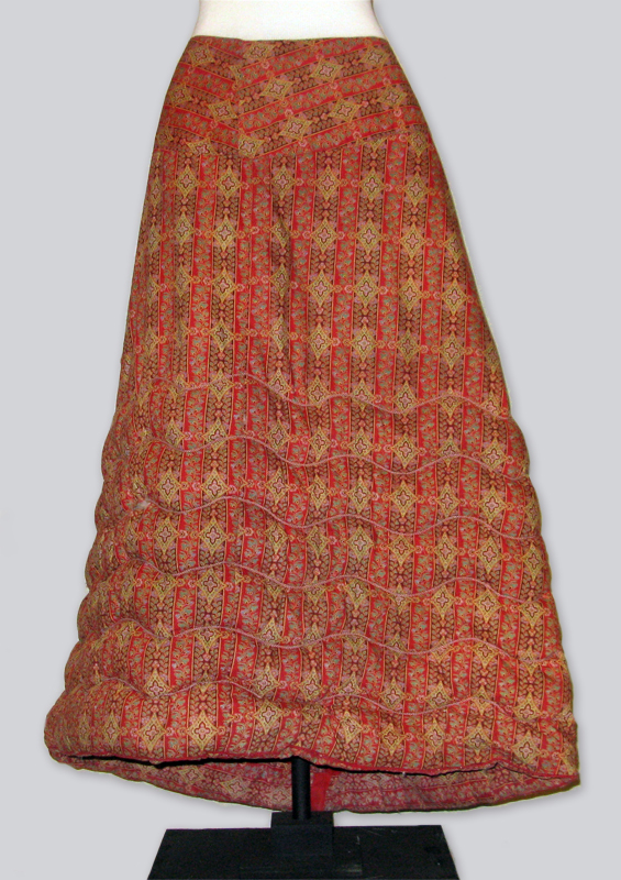 A red quilted petticoat with six rows of batting in the front compared with the nine in the back, providing greater comfort when seated.