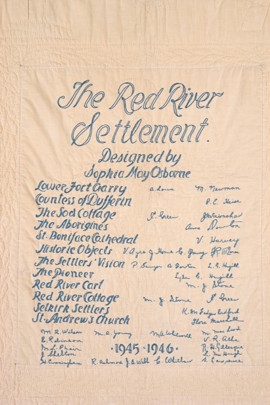 This cream coloured panel on the back of the quilt features the signatures of the creators in ornate blue writing.