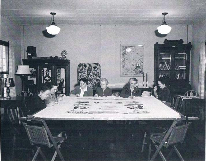 Six richly dressed women sewing parts of the quilt around an enormous work table in a large furnished room.