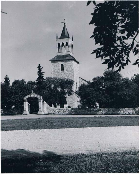 Historic photo of St. Andrews-on-the-Red Church, circa 1950, a simple white stone church depicted on a panel of the quilt.