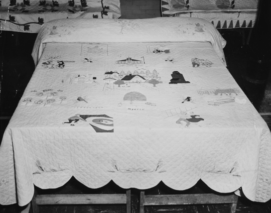 A large cotton quilt depicting scenes of life in Myrtle, Manitoba on a mock bed display soon after its creation.