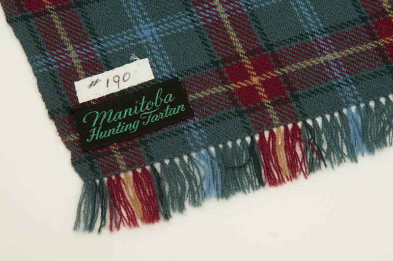 Detail view of the tartan and tag labeling it the 'Manitoba Hunting Tartan.'
