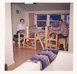 Designer Hugh K Rankine and his wife Dorothy sit opposite each other while weaving on floor looms at home.