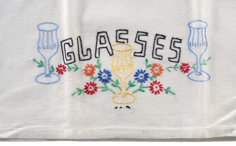 A tea towel made from a cotton flour sack, skillfully embroidered with stylized dinner table glasses and flowers.
