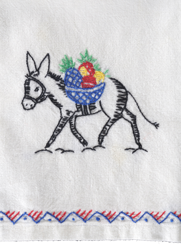 A tea towel made from a cotton flour sack, skillfully embroidered with the image of a donkey carrying tropical fruit.