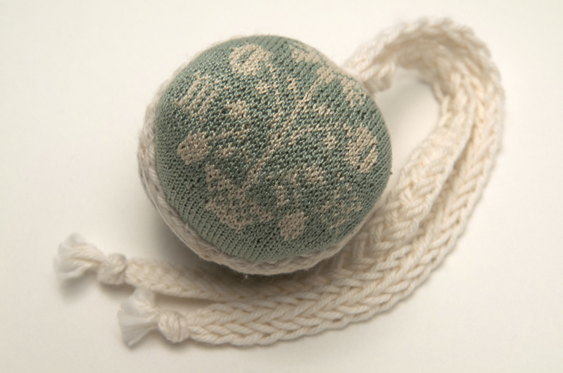 A small light green and white tightly knitted pinball with stylized geometric floral design with white tassels that hang from the top of the ball.
