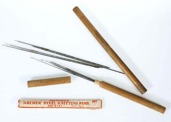 A selection of thin needle-like makkin wires, steel knitting pins with wood cylindrical packaging and label identifying them as Archer brand.
