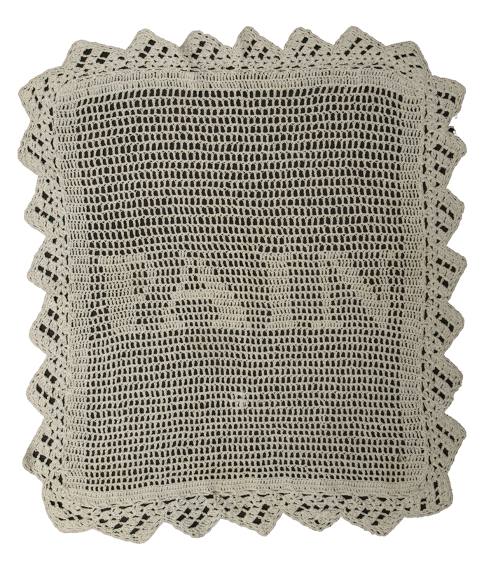 A white crocheted breadbasket liner made by Kathleen M. McKechnie with the letters P,A,I,N at the centre, representing the French word for bread.