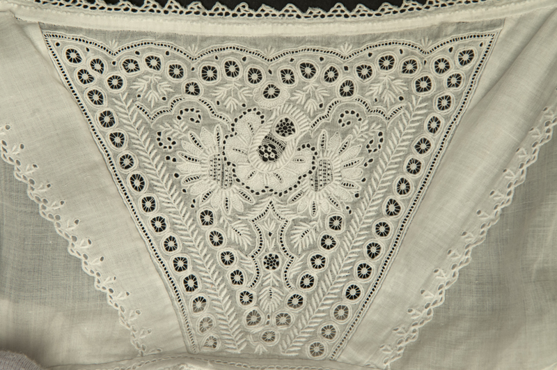 Detail view of white 19th century christening gown showing the delicate floral decorated Ayrshire style embroidery along the neckline.