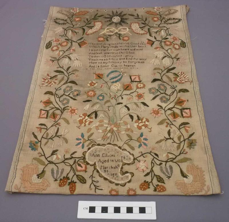 A sampler decorated with floral embroidery and a verse, created in 1811 by Ann Elliot, aged 14.
