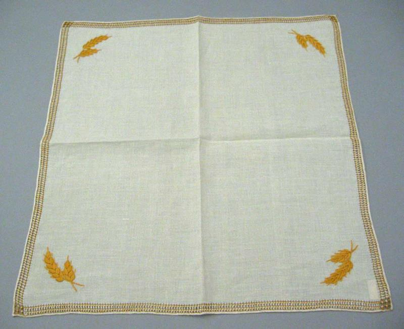 Square linen muffin cloth embroidered with the Crafts Guild of Manitoba's signature gold wheat pattern.