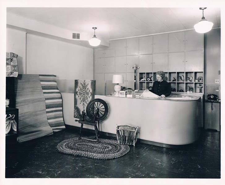 The Crafts Guild of Manitoba shop in 1956. A spinning wheel rests at the base of a large modern desk.
