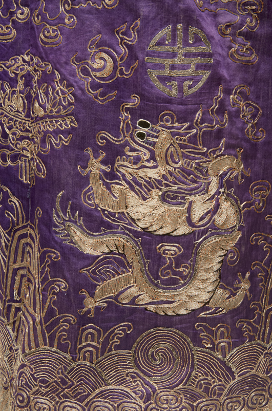 Detail showing an ornate four-clawed dragon in couched gold thread on a purple silk background.