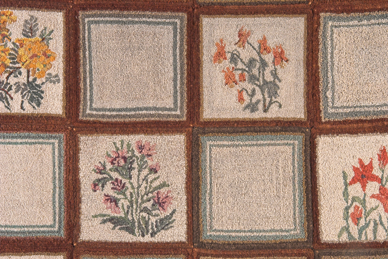 Close up of a squared hooked rug with warm coloured wildflowers in several of the squares on a white background.