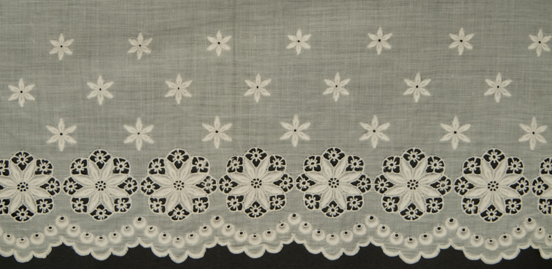 Detail view of the white cotton altar cloth showing floral style cutwork and satin stitch along the hem.