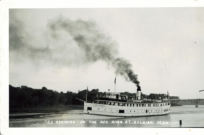 1950 photo of the steamboat SS Keenora on the Red River, black plumes of smoke billowing from its central stack.