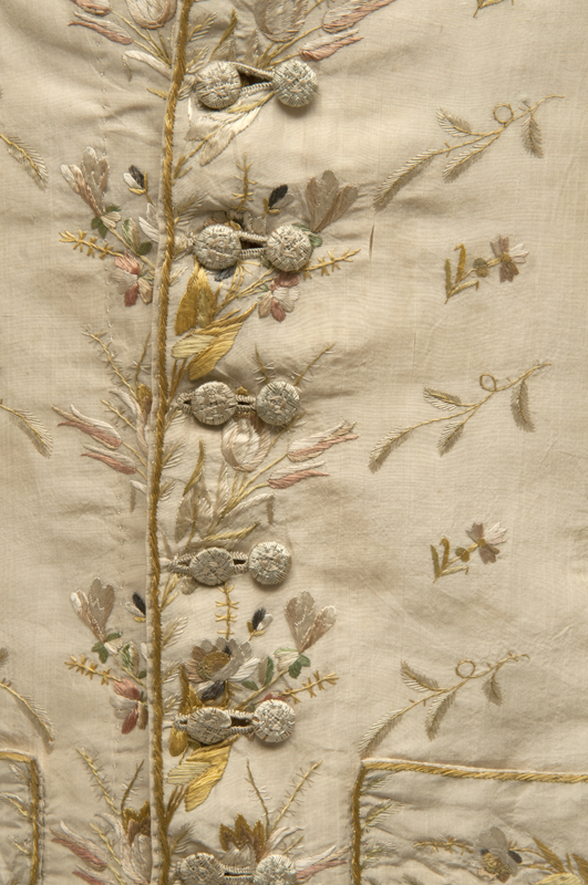 Detail view of an ornate cream coloured silk waistcoat showing the intricate pastel floral embroidery.