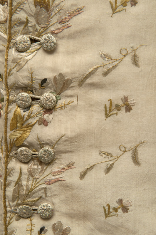 Detail view of an ornate cream coloured silk waistcoat showing the delicately embroidered cream buttons.