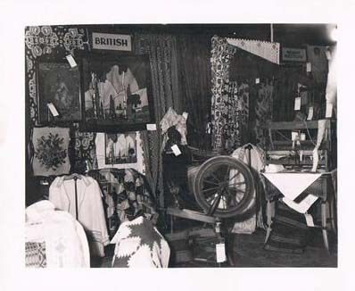 A Crafts Guild of Manitoba display exhibit showing several works of handicraft and clothing of British origin.