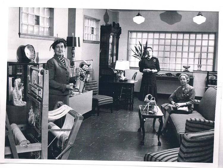 Three richly dressed women pose in a gift shop, circe 1956. Several glass cases and displays show craft goods for sale.
