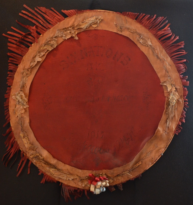 Ceremonial red dyed leather wreath in the shape of a drum, possibly sheepskin, fastened to a wooden frame.