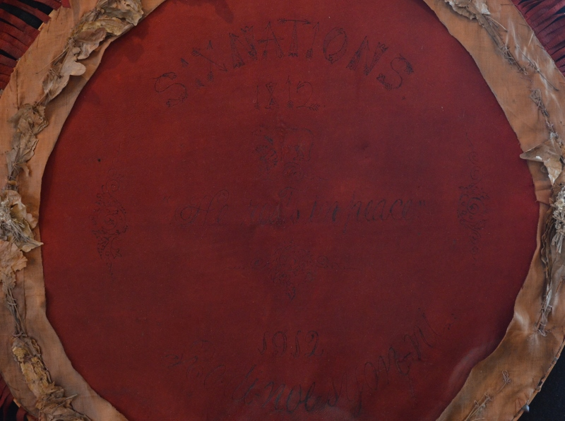 Detail view of the leather wreath with the words 'Six Nations 1812–1912 He Rests in Peace – Rodinosyonni.'