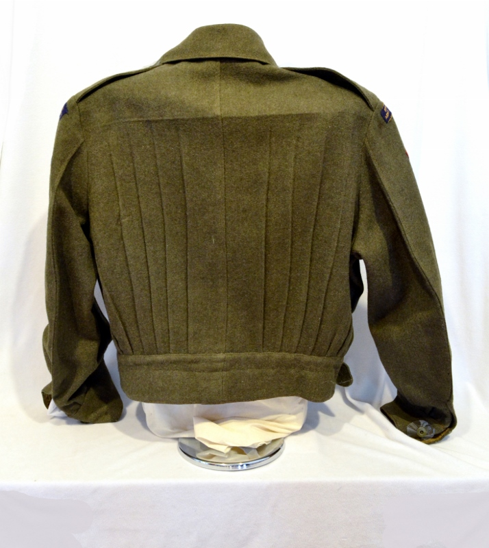 Rear view of green khaki wool uniform jacket with rank insignia and commendations, originally belonging to Harold Clement.