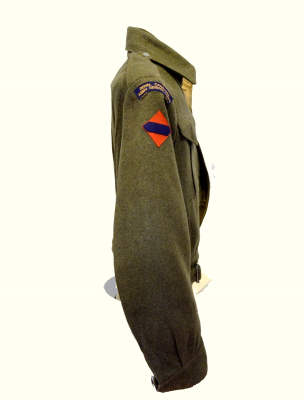 Side view of green khaki wool uniform jacket with rank insignia and commendations, originally belonging to Harold Clement.