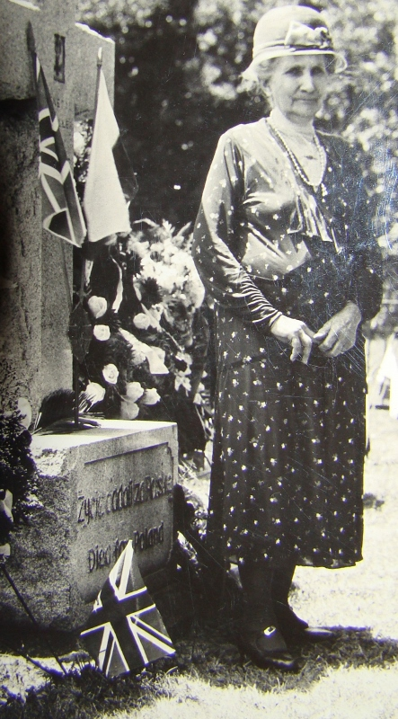 Posed photograph of Elizabeth Carr Ascher standing next to a stone cross memorial to Polish soldiers.