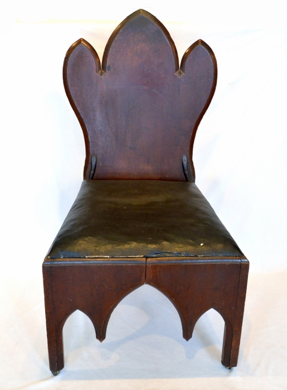 A dark black-walnut judge's chair with a worn brown leather cushion, crafted in the Neo-Gothic style.