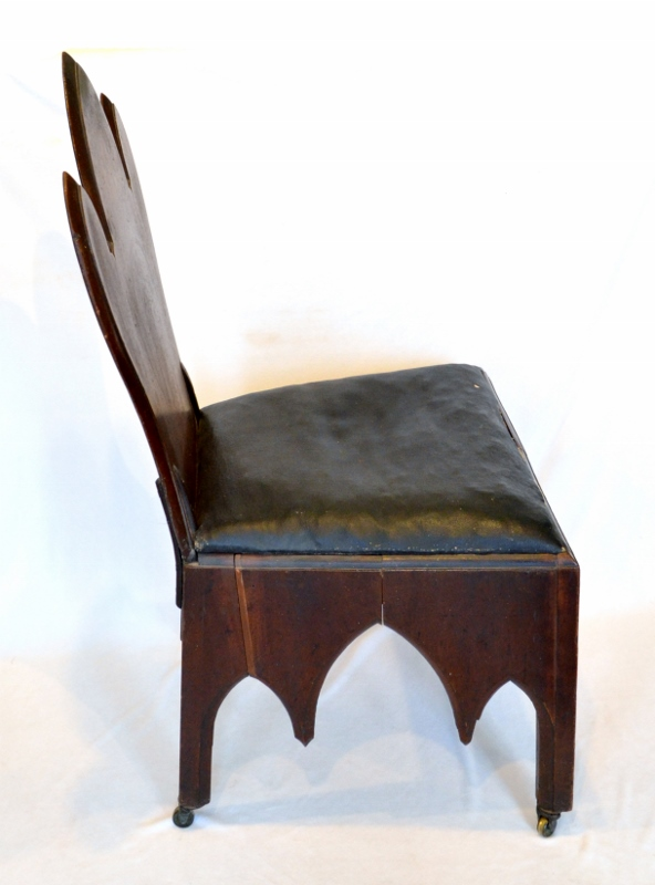 Side view of a dark black-walnut judge's chair with a worn brown leather cushion, crafted in the Neo-Gothic style.