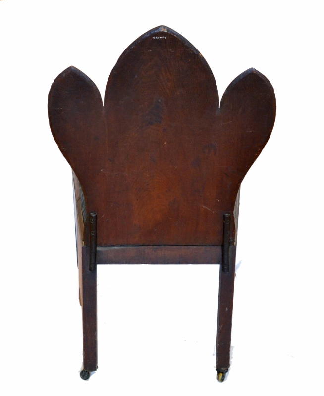 Rear view of a dark black-walnut judge's chair with a worn brown leather cushion, crafted in the Neo-Gothic style.