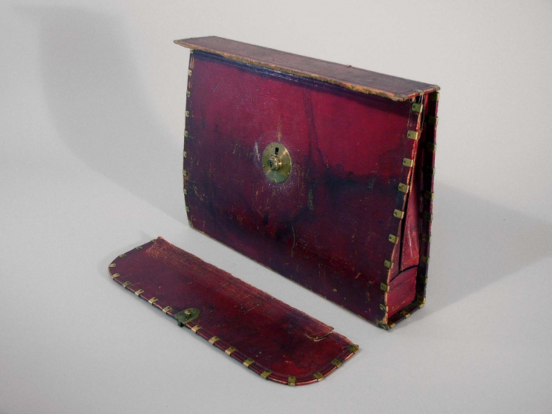 A dark red leather foldable dispatch case with polished brass lock and trim, owned by Loyalist William Claus in 1812.