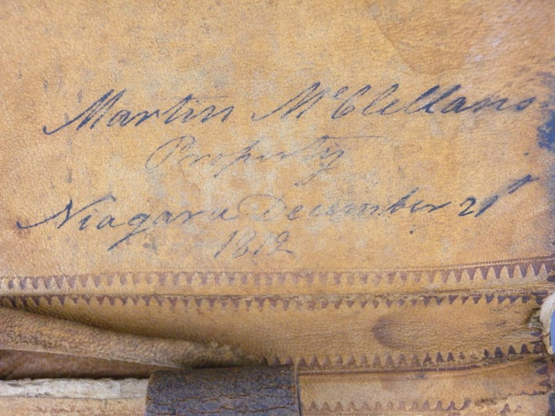 Detail view of inscription in light brown leather wallet with words 'Martin McClellan's Property Niagara December 21 1812'