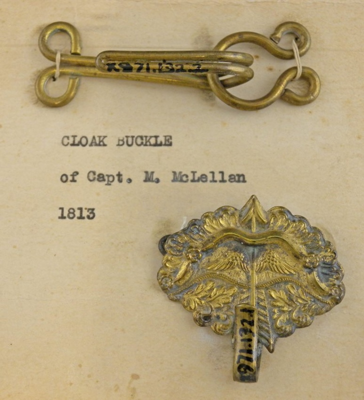 Ornate brass cloak buckle with bow and arrow design, owned by Captain Martin McClellan.