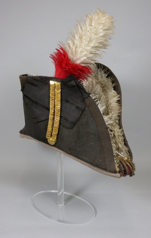 Anterior view of black bicorn hat with tall red and white feather plume and fur lining, owned by Sir Isaac Brock.