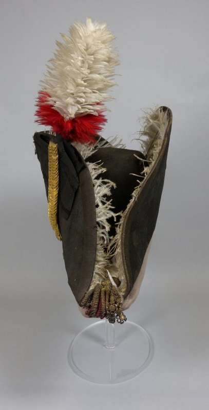 Front view of black bicorn hat with tall red and white feather plume and fur lining, owned by Sir Isaac Brock.