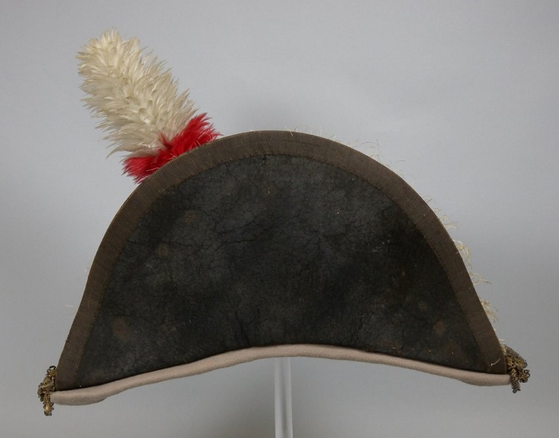 A black bicorn hat with tall red and white feather plume and fur lining, owned by Sir Isaac Brock.