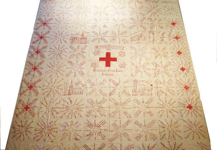 Large white quilt with an embroidered red cross and four local churches at center, surrounded by hundreds of red embroidered signatures.