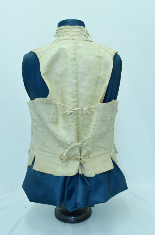 Rear view of silk waistcoat adorned with false pockets, floral trim, and steel beads, denoting the high status of its owner Robert Hamilton.
