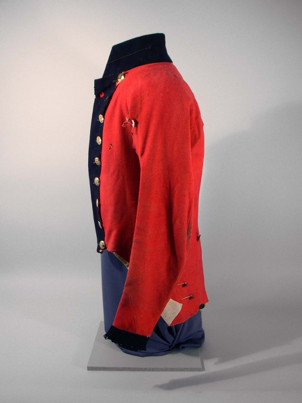 Side view of red military coat circa 1814 with blue navy trim and gold buttons, owned by Daniel McDougal.