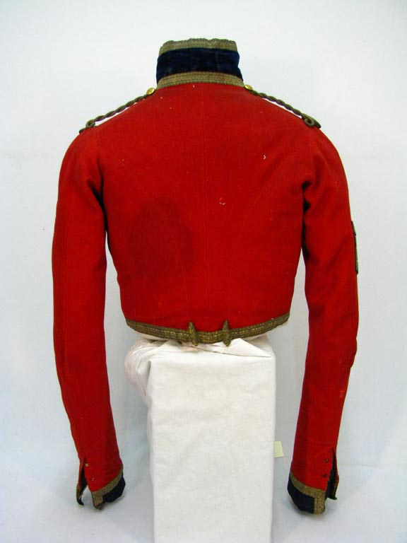 Rear view of scarlet military coat with gold buttons and trimmed with gold thread, owned by Sergeant-Major Adam Flanigan.
