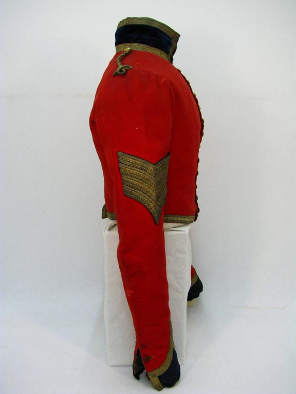 Side view of Rear view of scarlet military coat with gold buttons and trimmed with gold thread, owned by Sergeant-Major Adam Flanigan.
