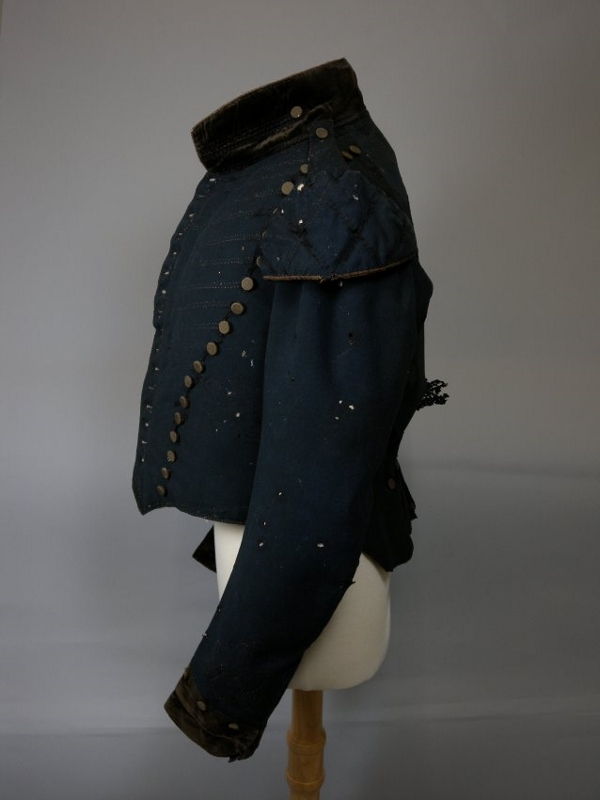 Side view of a dark green wool and velvet tunic with brass buttons, attributed to Donald McDougald circa 1812.